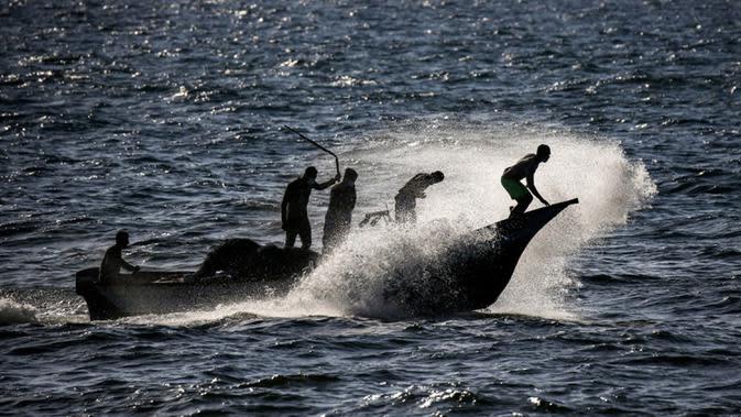 Nelayan Palestina naik perahu menerjang ombak saat menangkap ikan di Laut Mediterania, Rafah, Jalur Gaza, Rabu (2/9/2020). (SAID KHATIB/AFP)
