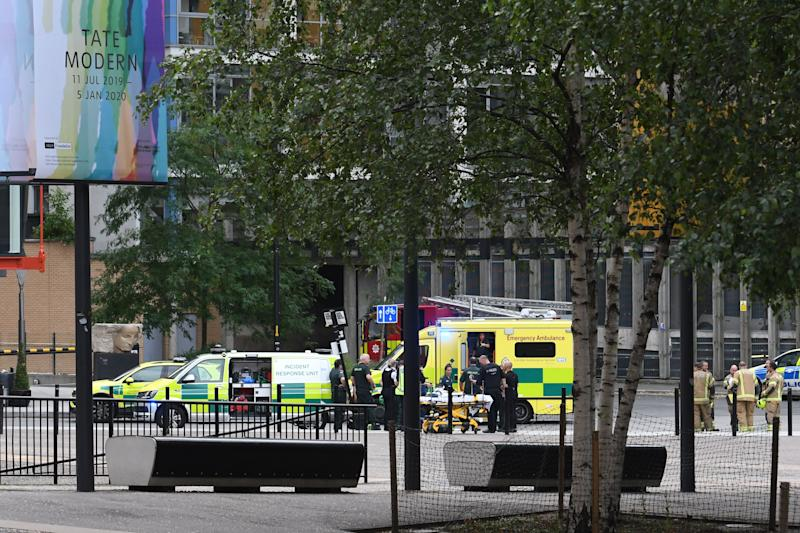 """Police, ambulance crews and fire crews are seen outside the Tate Modern gallery in London on August 4, 2019 after it was put on lock down and evacuated after an incident involving a child falling from height and being airlifted to hospital. - London's Tate Modern gallery was evacuated on Sunday after a child fell """"from a height"""" and was airlifted to hospital. A teenager was arrested over the incident, police said, without giving any details of the child's condition. (Photo by Daniel SORABJI / AFP) (Photo credit should read DANIEL SORABJI/AFP/Getty Images)"""