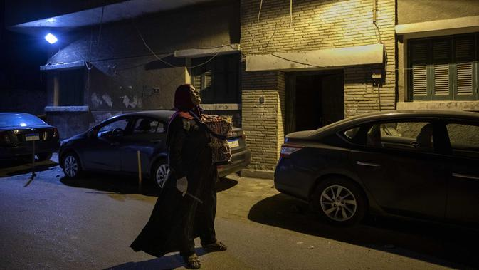 Seorang mesaharati Hajja Dalal (46) membangunkan warga untuk sahur saat bulan suci Ramadan di Kairo, Mesir, Rabu (29/4/2020). Namun saat ini, mesaharati agaknya akan menghadapi kepunahan mengingat sedikit orang yang tertarik untuk pekerjaan itu. (AP Photo/Nariman El-Mofty)