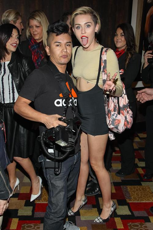 "Celebrity photographer Luis Martinez and singer Miley Cyrus arrive at the ""'Britney Spears: Piece of Me' Planet Hollywood Launch Party"", on Friday, Dec. 27, 2013, in Las Vegas. (Photo by Paul A. Hebert/Invision/AP)"