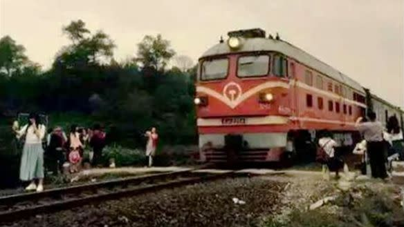 The woman was photographed posing dangerously close to the moving train. Photo: YouTube
