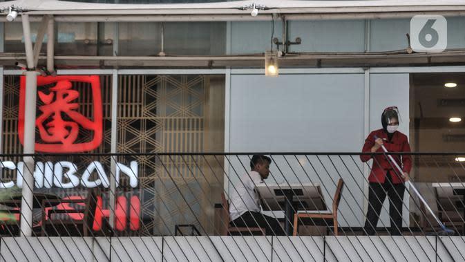Pekerja membersihkan area restoran kawasan Soedirman, Jakarta, Minggu (11/10/2020). Gugus Tugas Percepatan Penanganan Covid-19 mencatat adanya pelambatan kenaikan kasus positif atau aktif di Ibu Kota selama sebulan pemberlakukan PSBB yang diperketat. (merdeka.com/Iqbal S. Nugroho)