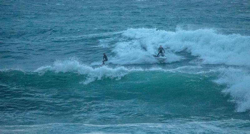 Surfer riding huge waves as wild wind hits the Sydney coastline Thursday evening.