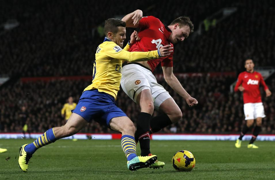 Arsenal's Wilshere challenges Manchester United's Jones during their English Premier League soccer match in Manchester