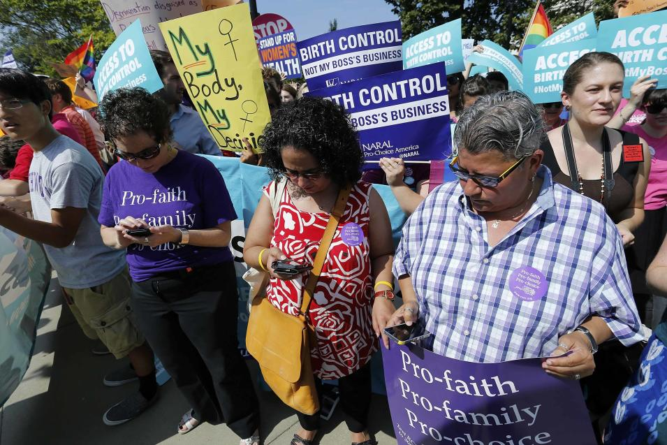 Demonstrators in support of abortion and contraceptive rights read on their mobile phones as the ruling for Hobby Lobby against their cause was announced outside the U.S. Supreme Court in Washington