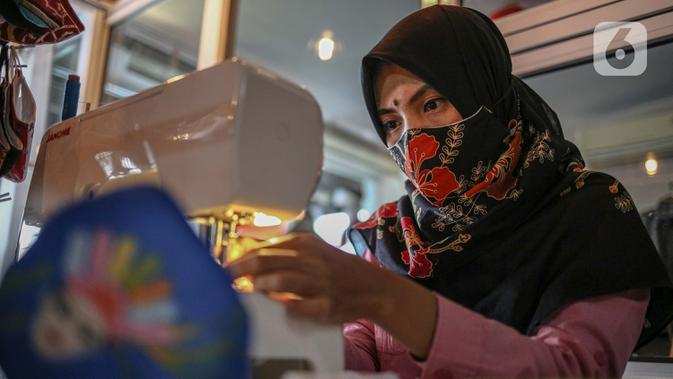 PEMBUATAN MASKER BATIK DI HARI BATIK NASIONAL 2020: Perajin menyelesaikan pembuatan masker batik di Butik Elemwe, Jakarta, (2/10/2020). Badan Standardisasi Nasional (BSN) mengeluarkan spesifikasi masker kain berSNI yang terbagi menjadi tiga tipe berdasarkan penggunaannya (Liputan6.com/Faizal Fanani)