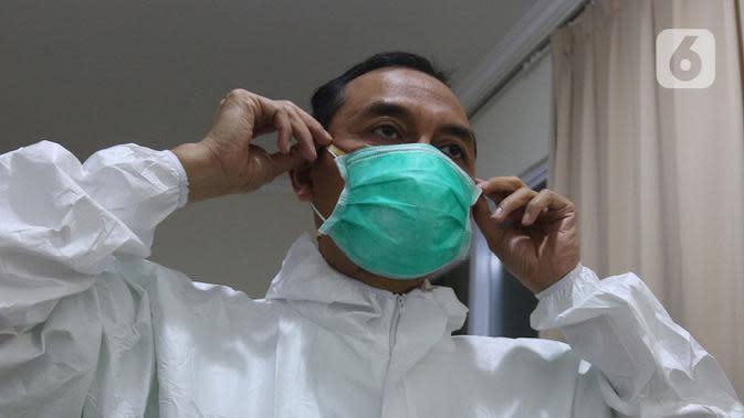 dr Rahmadi Iwan Guntoro, Sp.P melapisi masker N95 dengan masker bedah di Rumah Sakit Haji, Jakarta, Kamis (9/4/2020). Gugus Tugas Percepatan Penanganan COVID-19 telah mengeluarkan rekomendasi standar APD berdasarkan tiga tingkatan perlindungan. (Liputan6.com/Herman Zakharia)