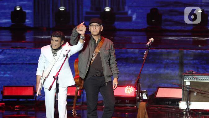 Penyanyi Rhoma Irama (kiri) dan Iwan Fals bergandengan tangan saat tampil dalam konser Pesta Perak 25 Indosiar di Jakarta, Minggu (12/1/2020). Rhoma Irama dan Iwan Fals berkolaborasi membawakan lagu Mirasantika, Buku Ini Aku Pinjam, Judi, dan Santai. (Liputan6.com/Herman Zakharia)