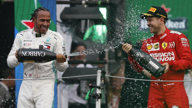 Pembalap Mercedes Lewis Hamilton, menyemprotkan sampanye ke arah pembalap Ferrari Sebastian Vettel setelah berhasil menjuarai balapan GP Meksiko di Autodromo Hermanos Rodriguez, Mexico City (28/10/2019). (AP Photo/Rebecca Blackwell)