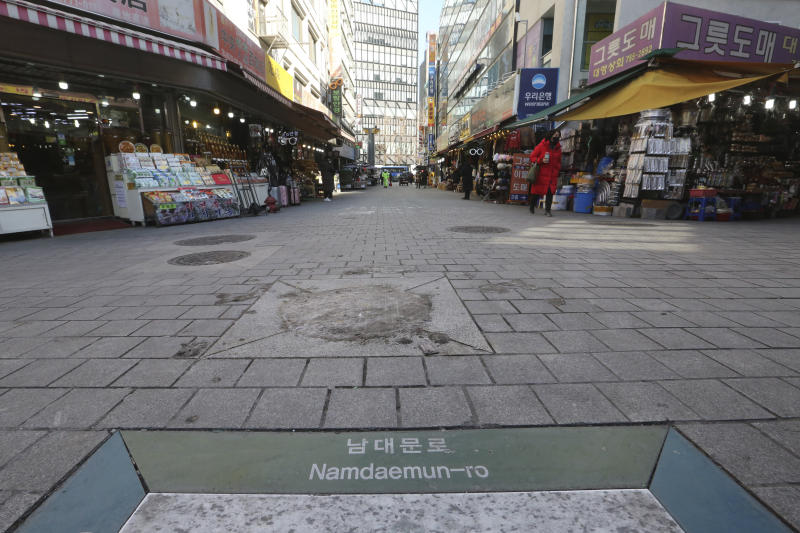 In this Tuesday, Feb. 18, 2020, photo, a woman wearing a face mask walks on the almost empty Namdaemun Market street in Seoul, South Korea. Even as cases and deaths from the new virus mount, fear is advancing like a tsunami - and not just in the areas surrounding the Chinese city of Wuhan, the center of the outbreak that has been declared a global health emergency. (AP Photo/Ahn Young-joon)