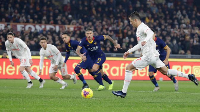 Pemain Juventus Cristiano Ronaldo (kanan) melakukan tembakan ke gawang AS Roma saat bertanding pada pekan ke-19 Liga Italia Serie A 2019-2020 di Stadion Olimpico, Minggu (12/1/2020). Juventus naik ke puncak klasemen usai menaklukkan AS Roma 2-1. (AP Photo/Andrew Medichini)