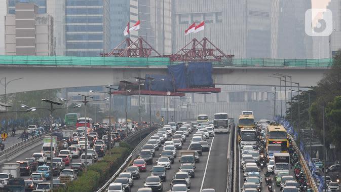 Kendaraan melintas berlatar pembangunan bentangan beton lintasan LRT di Jalan Gatot Subroto Jakarta, Kamis (7/11/2019). Menurut data website LRT Jabodebek, lintasan LRT Kuningan merupakan salah satu jembatan kereta lengkung dengan struktur beton terpanjang di dunia. (Liputan6.com/Immanuel Antonius)