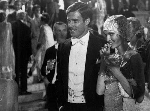 "FILE - This 1974 file photo originally released by Paramount Pictures shows Robert Redford as Jay Gatsby, and Mia Farrow as Daisy, in ""The Great Gatsby."" F. Scott Fitzgerald's ""The Great Gatsby"" is short, almost novella size. It features larger-than-life characters, glamorous extravagance and dramatic deaths. On its surface, it's almost certainly the most Hollywood-friendly of the great American novels. But the poetry of ""Gatsby"" has remained largely locked on the page. Since it was published in 1925, it has been staged as a play and a musical, spawned four previous film adaptations and even been made into an 8-bit Nintendo-style video game in with Nick Carraway must evade cocktail-dispensing butlers and flappers while trying to find Gatsby. On May 10, 2013, Baz Luhrmann will release his ""Gatsby,"" a 3-D blockbuster spectacle with a star-studded cast, a contemporary soundtrack and hopes of cracking the code of Fitzgerald's mysterious novel. (AP Photo/ Paramount Pictures, File)"