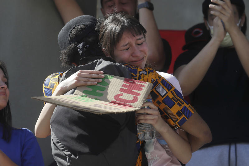 In this June 2, 2020 file photo Tiffany Medrano Martinez, 14, right, is hugged by Dez Frazier after speaking at a protest over the death of George Floyd in Redwood City, Calif. Many have seen on video a consistent drumbeat of deaths of people of color at the hands of police since they were children. They also have native fluency in social media, where information and communication can translate quickly into real-life action. Now, in big cities and small towns, whether liberal or conservative, the new young organizers are taking matters into their own hands and bringing together hundreds or thousands of people to peacefully press for change. (AP Photo/Jeff Chiu)