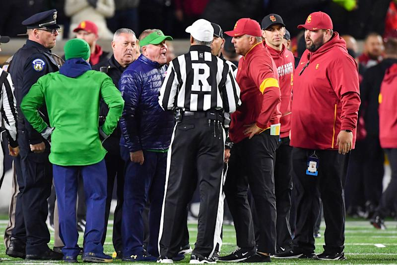 Oct 12, 2019; South Bend, IN, USA; Notre Dame Fighting Irish head coach Brian Kelly and USC Trojans head coach Clay Helton talk with referee Michael Mothershed after both teams were penalized for unsportsmanlike conduct after as the first half ended at Notre Dame Stadium. Mandatory Credit: Matt Cashore-USA TODAY Sports