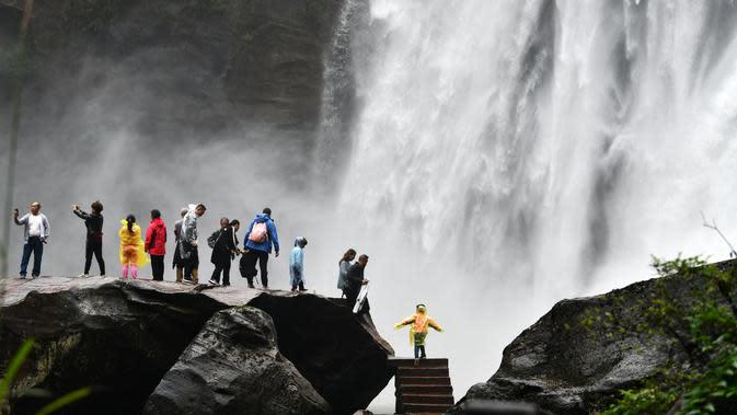 Sejumlah wisatawan mengamati air terjun Chishui di Kota Zunyi, Provinsi Guizhou, China barat daya (7/10/2020). Terkenal karena kekayaan sejarah dan sumber daya alamnya, Kota Zunyi menarik banyak wisatawan selama libur Hari Nasional dan Festival Pertengahan Musim Gugur. (Xinhua/Yang Wenbin)