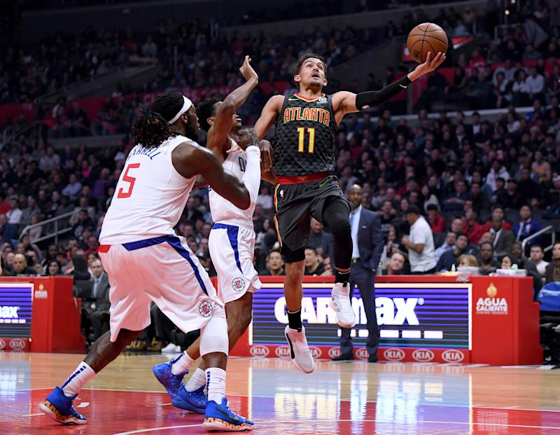 LOS ANGELES, CALIFORNIA - JANUARY 28: Trae Young #11 of the Atlanta Hawks scores on a layup past Shai Gilgeous-Alexander #2 and Montrezl Harrell #5 of the LA Clippers during the first half at Staples Center on January 28, 2019 in Los Angeles, California. (Photo by Harry How/Getty Images)