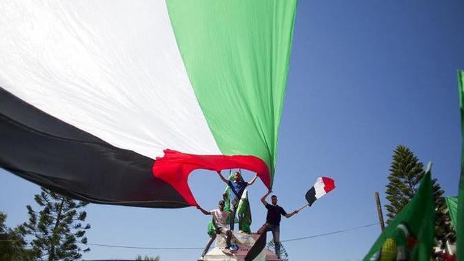 Warga Palestina membentang bendera negara mereka, bergembira menyambut rekonsiliasi antara Hamas dan Fatah (AP Photo/Khalil Hamra)