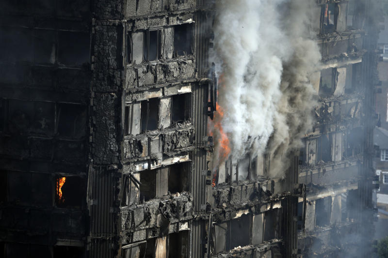 FILE - In this file photo dated Wednesday, June 14, 2017, The Grenfell Tower apartment block burns hours after a deadly blaze swept through the high rise apartment block in London.  A report is due to be released Wednesday Oct. 30, 2019, following a far reaching inquiry into the deadly apartment block fire. (AP Photo/Alastair Grant, FILE)