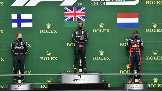 Pembalap Mercedes Lewis Hamilton (tengah) berdiri di podium usai menempati posisi pertama Formula 1 Grand Prix di Spa-Francorchamps, Spa, Belgia, Minggu (30/8/2020). Posisi kedua dan ketiga diisi pembalap Mercedes Valtteri Bottas serta pembalap Red Bull Max Verstappen. (John Thys, Pool via AP)