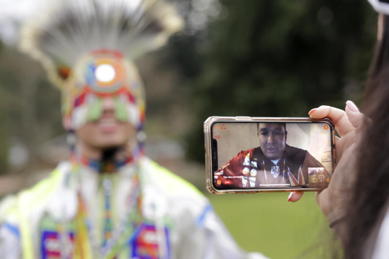 In this photo taken Saturday, April 4, 2020, moderator Whitney Rencountre, a Crow Creek Dakota tribal member, is seen on a screen from Rapid City, S.D., as he talks with Wakiyan Cuny, a Dakota and Lakota tribal member, during a live streamed powwow, in Puyallup, Wash. The largest powwows in the country have been canceled or postponed amid the spread of the coronavirus. Tribal members have found a new outlet online with the Social Distance Powwow. They're sharing videos of colorful displays of culture and tradition that are at their essence meant to uplift people during difficult times. (AP Photo/Elaine Thompson)