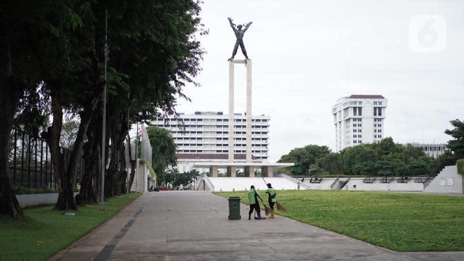 Petugas kebersihan membersihkan Taman Lapangan Banteng terlihat di Jakarta, Minggu (20/9/2020). Seluruh taman kota dan hutan kota ditutup kembali untuk sementara terkait pemberlakuan PSBB total di Jakarta guna menekan penyebaran virus covid-19. (Liputan6.com/Immanuel Antonius)