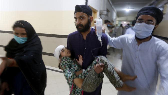 Sejumlah orang membawa gadis yang terluka dalam kecelakaan bus dan kereta api di Sheikhupura, Pakistan, Jumat (3/7/2020). Tidak ada penumpang kereta yang terluka dalam kecelakaan tersebut. (AP Photo/K.M. Chaudary)