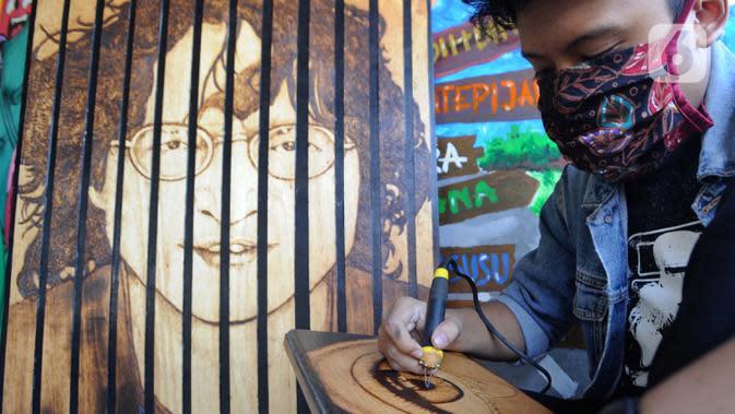 Anak Arfan (55) menyelesaikan karya seni lukis bakar di galeri Rumah Oenik, Kampung Ragamukti, Bogor, Senin (28/9/2020). Menggunakan limbah kayu dan kulit yang tidak terpakai Arfan mengubah dengan menggunakan solder listrik menjadi karya seni yang bernilai tinggi. (merdeka.com/Arie Basuki)