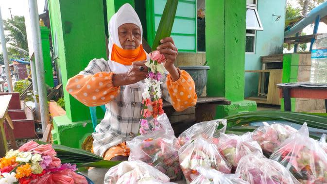 Nenek Nuryana berusia 78 tahun tetap menggeluti usaha kembang kuburan di TPU Kandang Kawat Palembang di tengah pandemi Corona Covid-19 (Liputan6.com / Nefri Inge)
