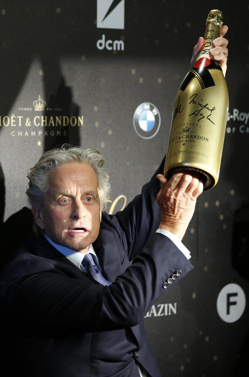 US actor Michael Douglas lifts a bottle of champagne as he arrives for the German premiere of the movie 'Behind The Candelabra' in Berlin, Germany, Monday, Sept. 2, 2013. (AP Photo/Michael Sohn)