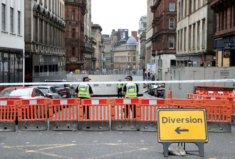 Police officers stand near the scene of reported multiple stabbings at West George Street in Glasgow