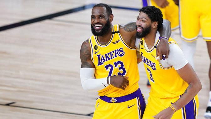 Pebasket Los Angeles Lakers, LeBron James dan Anthony Davis, merayakan kemenangan atas Denver Nuggets pada laga NBA di The Arena, Senin (11/8/2020). LA Lakers menang dengan skor 124-121. (AP Photo/Ashley Landis, Pool)