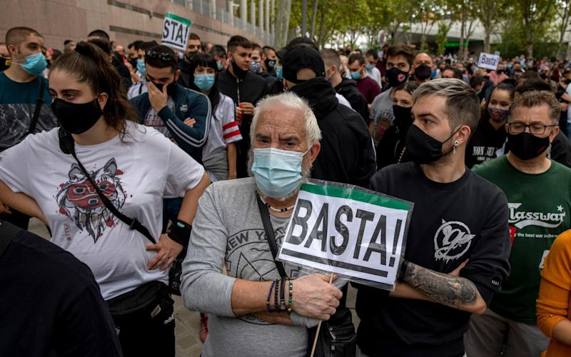Protesters wearing protective masks shout slogans as one holds a placard reading 'Enough' during a demonstration against the measures imposed by the regional government on areas with the most Covid cases - ablo Blazquez Dominguez/Getty Images