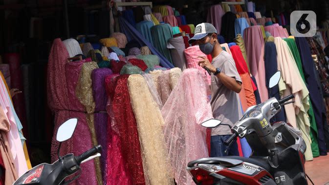 Aktivitas perdagangan tekstil di Pasar Cipadu, Tangerang, Senin (21/9/2020). Asosiasi Pertekstilan Indonesia (API) menyatakan industri Tekstil dan Produk Tekstil (TPT) sudah mulai beroperasi meski belum normal kembali akibat daya beli yang masih rendah di masa pandemi. (Liputan6.com/Angga Yuniar)