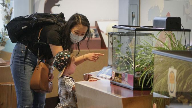 Seorang pekerja garis depan dan anaknya mengunjungi Science World di Vancouver, British Columbia, Kanada (23/7/2020). Science World Vancouver menawarkan tiket masuk gratis bagi para pekerja yang berjuang di garis depan melawan pandemi COVID-19 dan anggota keluarga mereka. (Xinhua/Liang Sen)