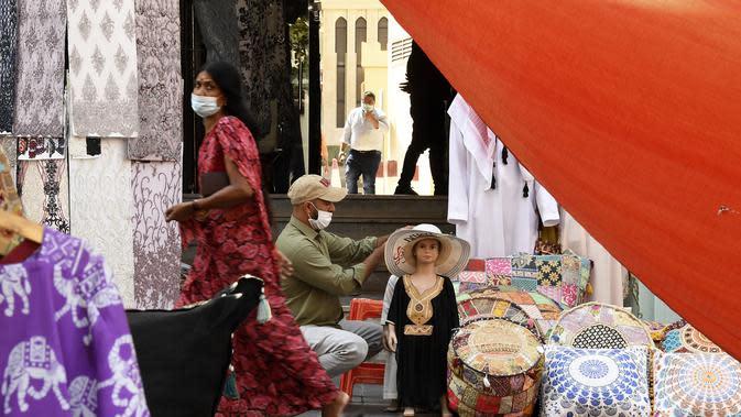 Seorang wanita mengenakan masker berjalan di Deira Souk di Teluk Emirat Dubai (30/9/2020). Barang yang dijual di Deira Souk juga paling diminati turis seperti rempah dan emas. (AFP/Karim Sahib)