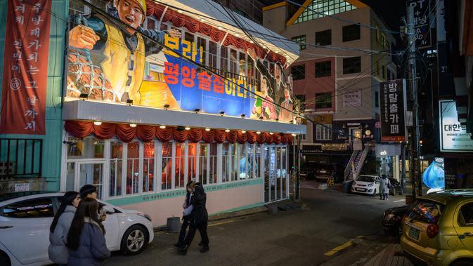 Warga berjalan melewati Pyeongyang Bar di Distrik Hongdae, Seoul, Korea Selatan, Jumat (10/1/2020). Pyeongyang Bar adalah satu-satunya bar bertema Korea Utara di Seoul. (ED JONES/AFP)