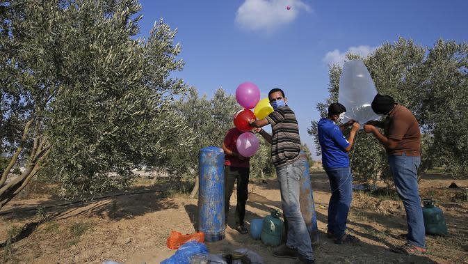 Sejumlah pria Palestina menyiapkan balon dengan alat peledak yang akan diterbangkan ke Israel disepanjang perbatasan Israel-Jalur Gaza (12/8/2020). Serangan balon api yang dilancarkan menyebabkan terjadinya puluhan kebakaran di areal pertanian Israel. (AFP Photo/Mohammed Abed)