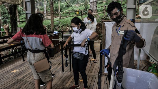 Petugas saat membantu pengunjung mengenakan tali pengaman sebelum melintasi Jembatan Gantung Situ Gunung, Sukabumi, Jawa Barat, Minggu (20/9/2020). (merdeka.com/Iqbal S. Nugroho)