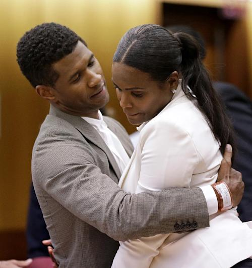 FILE - In this Friday, Aug. 9, 2013 file photo, R&B singer Usher, left, embraces ex-wife Tameka Foster Raymond after a judge dismissed an emergency request by Raymond seeking temporary custody of their two children, in Atlanta. Usher's son has been released from the hospital after nearly drowning in an Atlanta pool. A lawyer for the boy's mother said Tuesday, Aug. 13, 2013, that 5-year-old Usher Raymond V was released from Children's Healthcare of Atlanta Scottish Rite on Sunday. Attorney Angela Kinley said Tameka Foster Raymond saw her son at school Monday when he attended orientation for the new year. (AP Photo/David Goldman, File)
