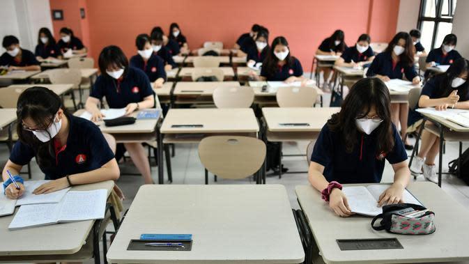 Siswa dengan mengenakan masker duduk di dalam ruang kelas di sekolah Marie Curie di Hanoi, Senin (4/5/2020). Vietnam membuka kembali aktivitas sekolah yang ditutup selama tiga bulan setelah dilaporkan tidak ada kasus virus corona COVID-19 baru hingga Sabtu, 2 Mei 2020. (Manan VATSYAYANA/AFP)