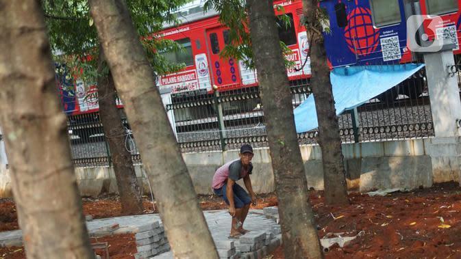 Pekerja menyelesaikan pembuatan jogging track di Taman Citra PPSU Srengseng Sawah, Jakarta, Rabu (4/12/2019). Jogging track dibuat guna meningkatkan kenyamanan bagi warga yang ingin beraktivitas di taman tersebut. (Liputan6.com/Immanuel Antonius)