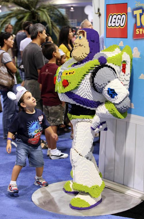FILE - In this Sept. 14, 2009 handout photo provided by The Lego Group, children look at Buzz Lightyear made of LEGO bricks at the D23 convention in Anaheim, Calif. The Walt Disney Co. is cracking open the vault, rolling out the red carpet and pulling back the curtain for more than 45,000 expected fans at this weekend's D23 Expo, Aug. 9-11, 2013, a three-event celebration of all things Disney at the Anaheim Convention Center. (AP Photo/The Lego Group, Rene Macura, File)