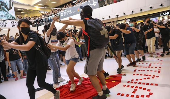 Protesters deface the Chinese national flag after gathering for a so-called sing-along protest at New Town Plaza in Sha Tin in September. Photo: Nora Tam