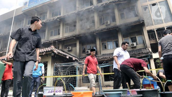 Sejumlah guru, pegawai, dan siswa mengisi air ke dalam wadah saat berusaha memadamkan api yang kembali muncul di Gedung SMK Yadika 6, Jatiwaringin, Pondok Gede, Kota Bekasi, Jawa Barat, Selasa (19/11/2019). Api muncul di salah satu ruang yang berada di lantai 2. (merdeka.com/Iqbal Nugroho)