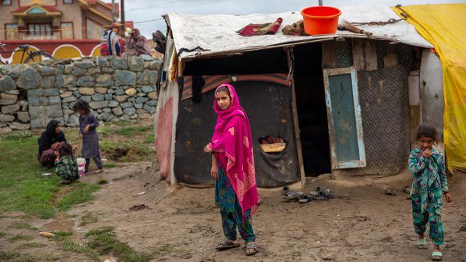 Gadis Kashmir Bakarwal menyaksikan berdiri di luar kamp sementara di pinggiran Srinagar, India, 31 Agustus 2020. Suku Bakarwals adalah kaum penggembala nomaden di Jammu Kashmir, yang berpindah-pindah untuk mencari padang rumput yang baik untuk ternak mereka. (AP Photo/Dar Yasin)