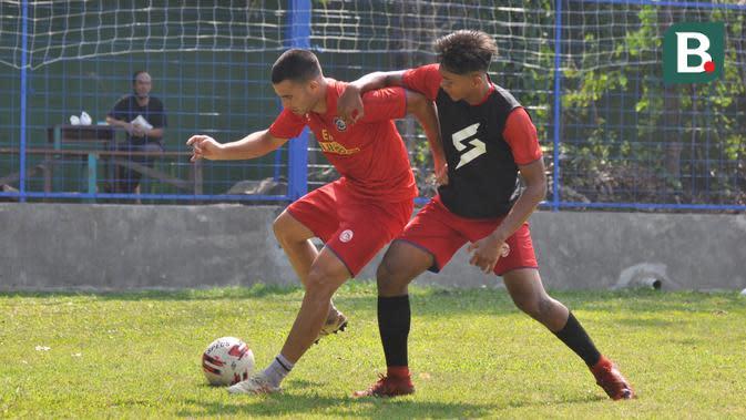 Striker Arema FC, Elias Alderete, mendapatkan pengawalan ketat dari Titan Fawazzi dalam internal game yang digelar Sabtu (5/9/2020) pagi. (Bola.com/Iwan Setiawan)