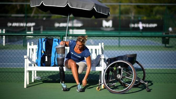Atlet para tenis Prancis Pauline Deroulede (kiri) menyaksikan sesi latihan turnamen tenis kursi roda French Riviera Open edisi ke-4 di Biot, 28 September 2020. Korban kecelakaan itu kehilangan kaki kirinya pada Oktober 2018. (FRANCK FIFE/AFP)