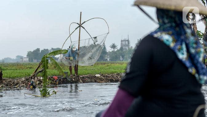 Warga mencari ikan betik menggunakan perangkap ikan tradisional atau anco di Kali Doser, Desa Wates, Bekasi, Jawa Barat, Selasa (21/1/2020). Hujan besar yang turun menjadi berkah bagi warga karena aliran air Kali Doser akan meluap dan menjadikan tangkapan melimpah. (merdeka.com/Imam Buhori)
