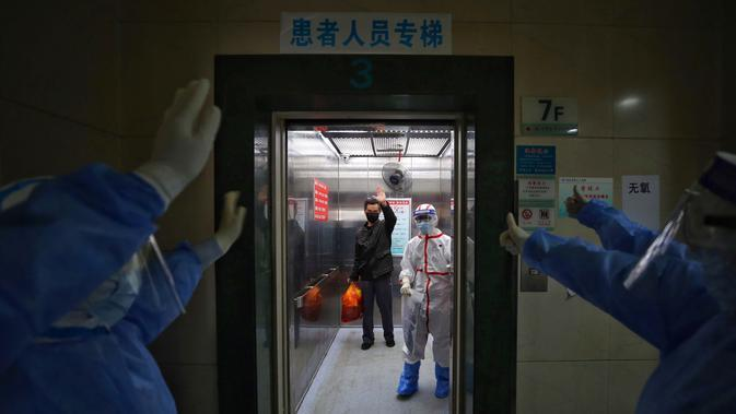 Petugas medis melambaikan tangan kepada pasien yang terjangkit virus corona COVID-19 di Rumah Sakit Palang Merah di Wuhan, Provinsi Hubei, China, 16 Maret 2020. Kasus baru pasien terinfeksi virus corona COVID-19 di negara yang menjadi pusat penyebaran pandemi ini mulai menurun. (Photo by STR/AFP)